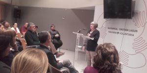 Mariluz Sanz, interviniendo en el acto y personas escuchando