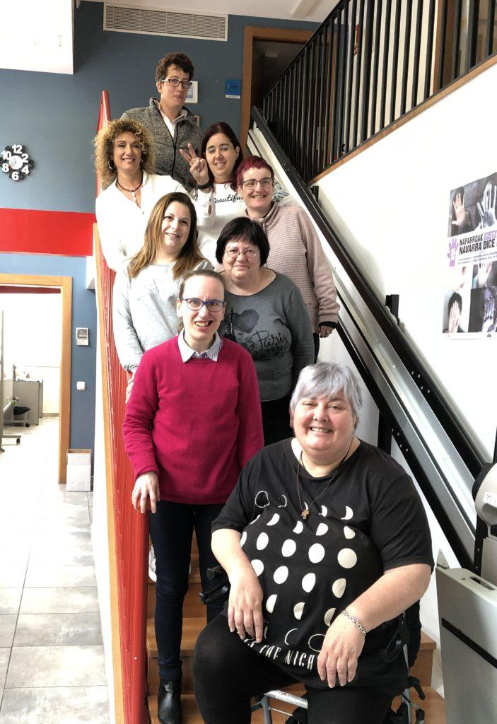 8 mujeres en una escalera mirando hacia la cámara